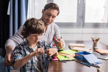 Father and son playing with atoms model