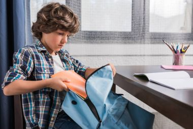 child packing backpack for school