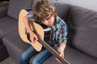 child playing acoustic guitar