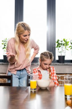 mother feeding daughter at breakfast