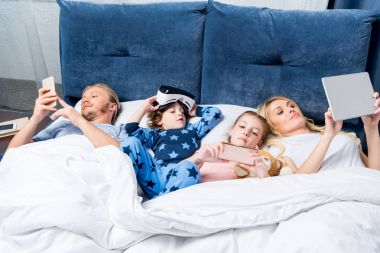 family with gadgets in bed
