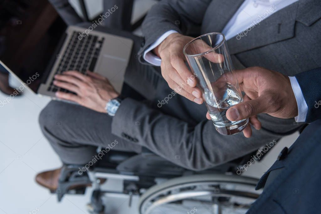 businessman giving glass of water to colleague