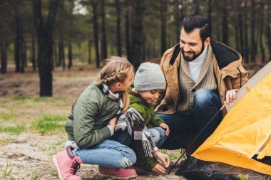 father and kids installing camping tent