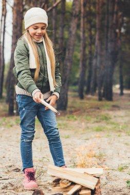 girl adding wood to bonfire