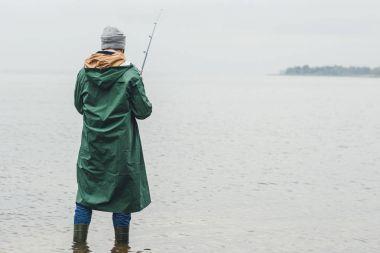 Lonely man fishing on rainy autumn day stock vector