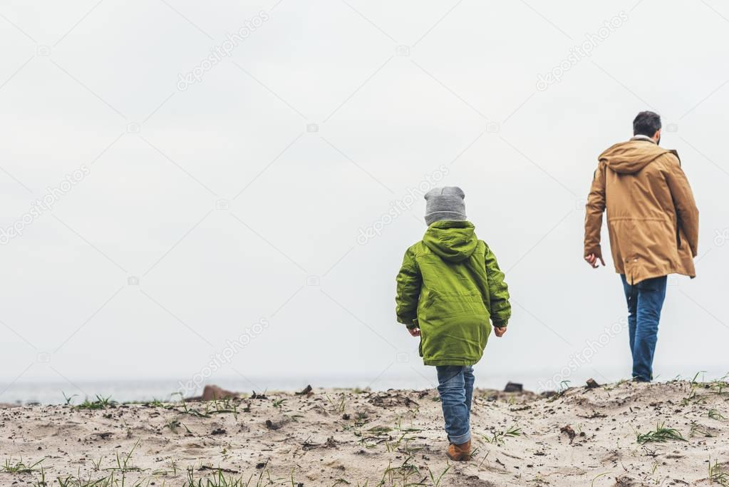 father and son walking by sandy beach