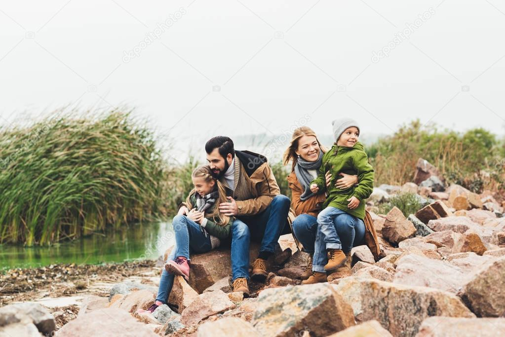 family sitting on rocky coast