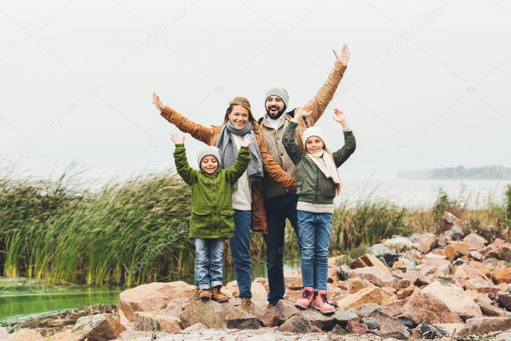 family standing on rocky coast