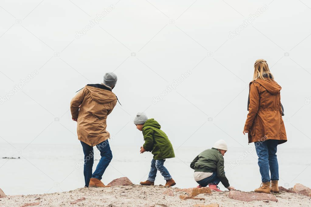 family throwing stones at sea