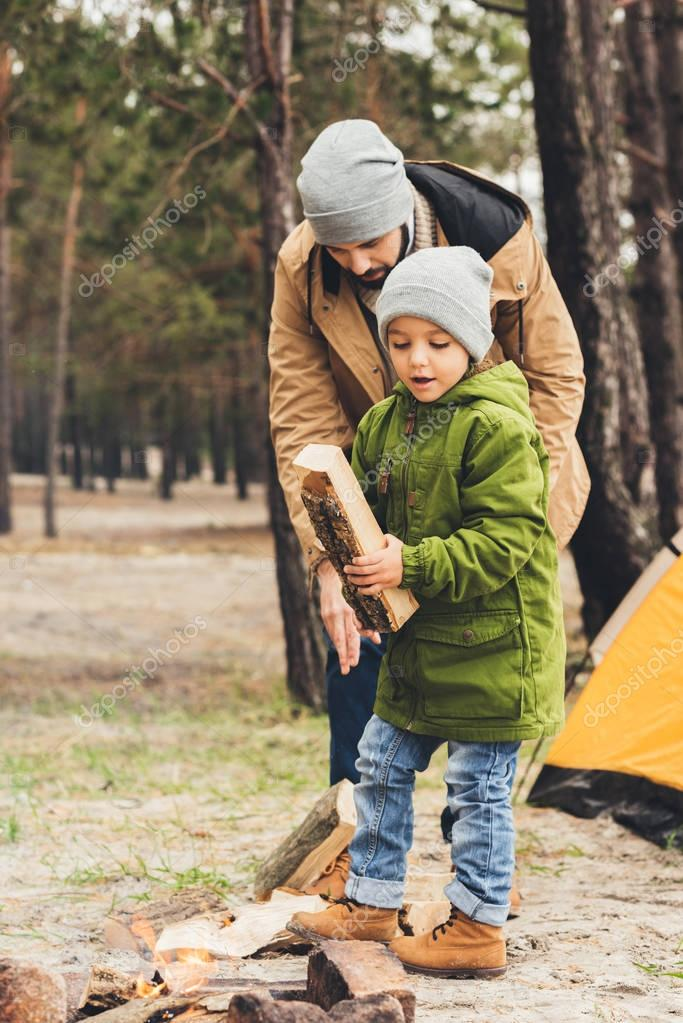 father and son with wood for bonfire