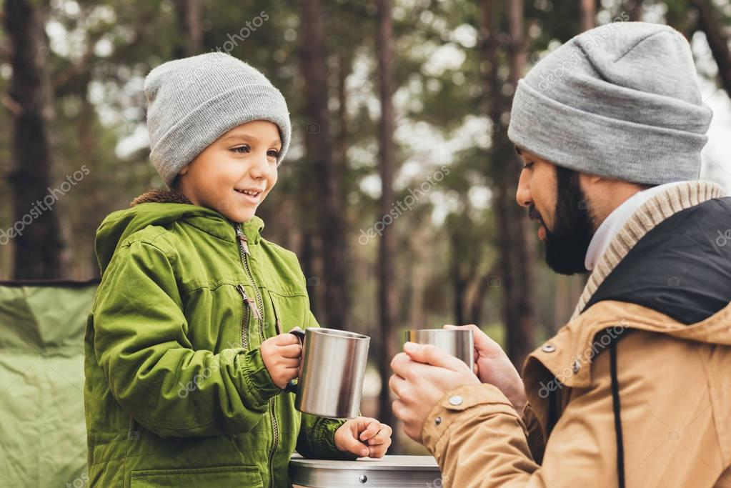 father and son with cups of tea outdoors