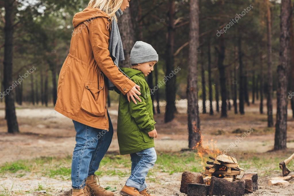 mother and son looking at campfire