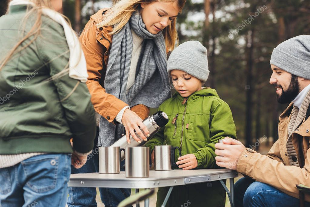 mother pouring tea from thermos for kids