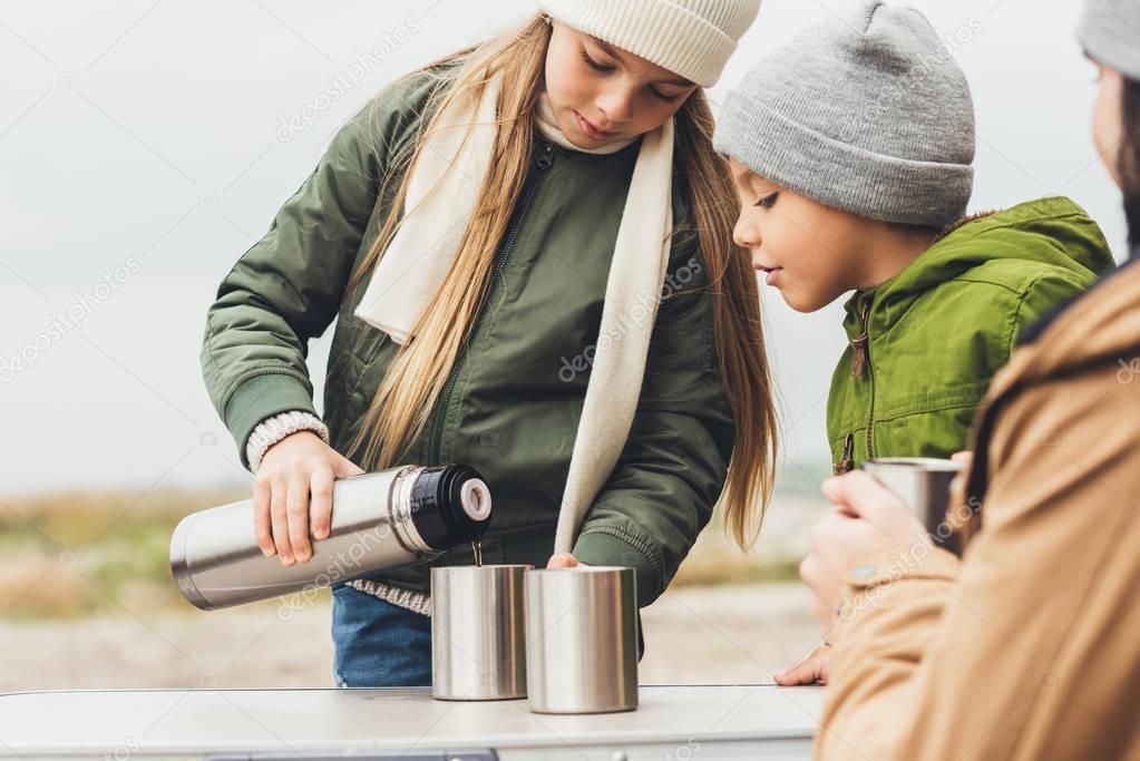 girl pouring tea for brother and father