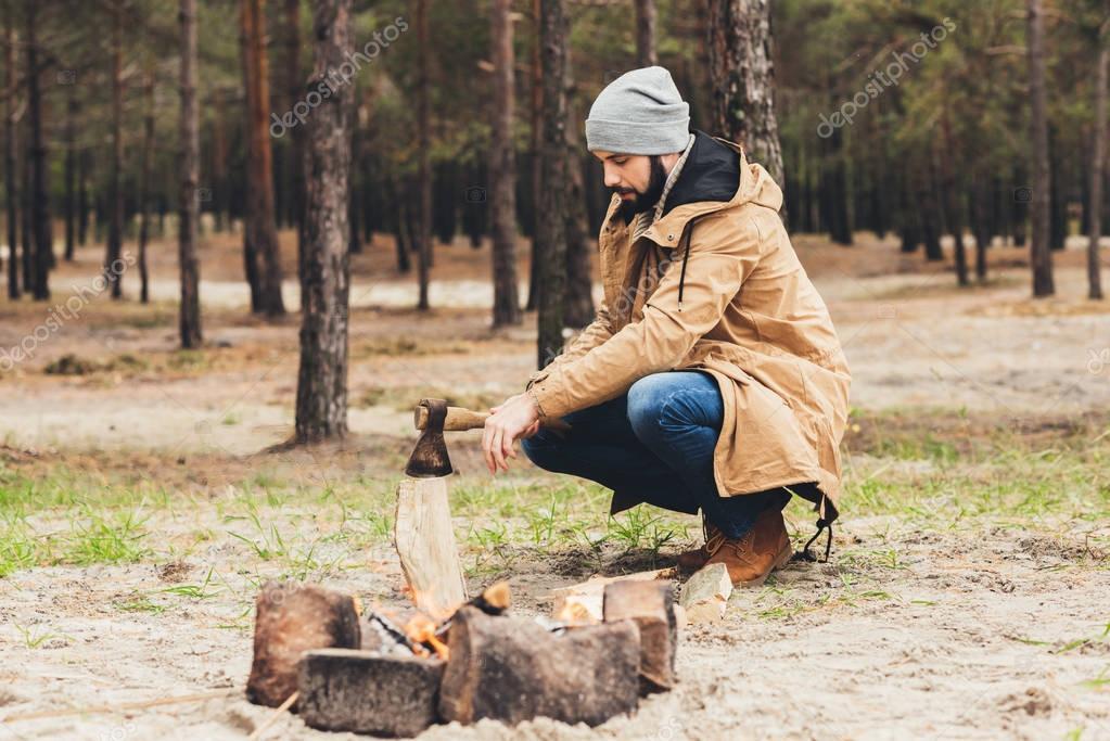 man cutting wood for bonfire