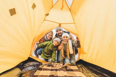 family looking at camping tent