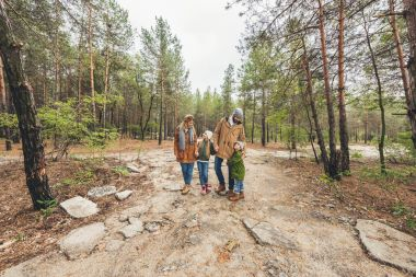 family standing on forest pathway