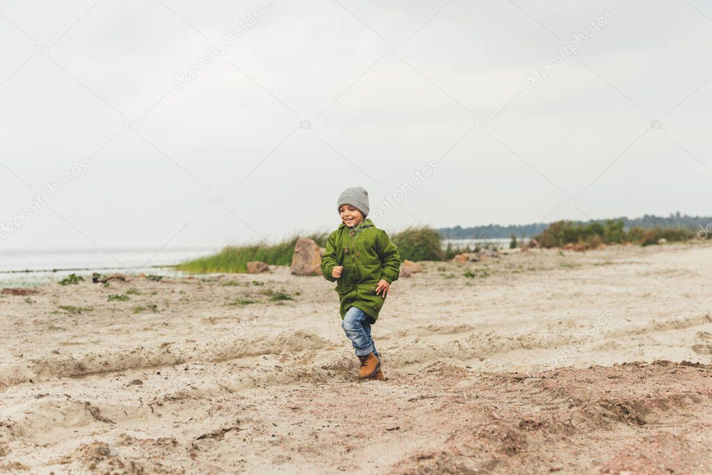 boy running by sandy beach