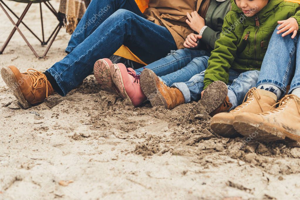 family sitting on sand