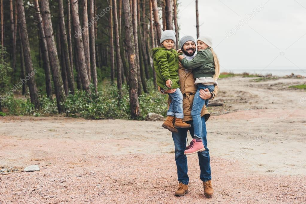 father and kids having fun on nature