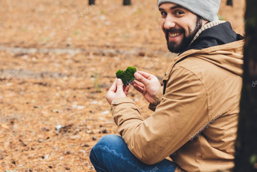 man holding piece on moss