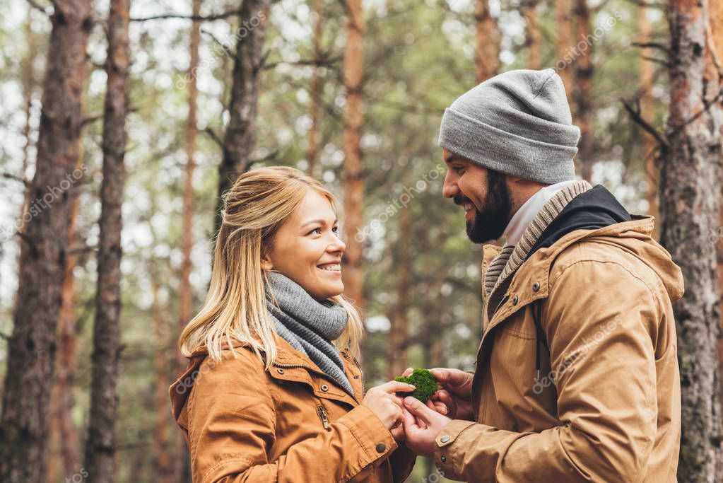 couple touching moss at forest