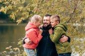 glücklicher Vater und Kinder im Park umarmt