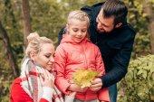 Fotografie Rodina drží podzimní listí v parku