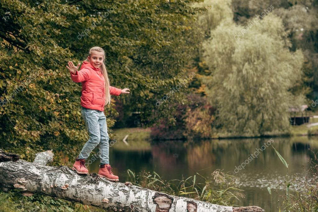 child walking on log in park