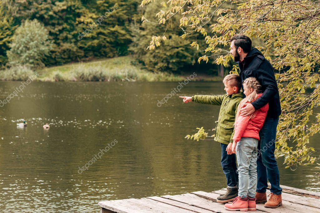 father with children looking at lake