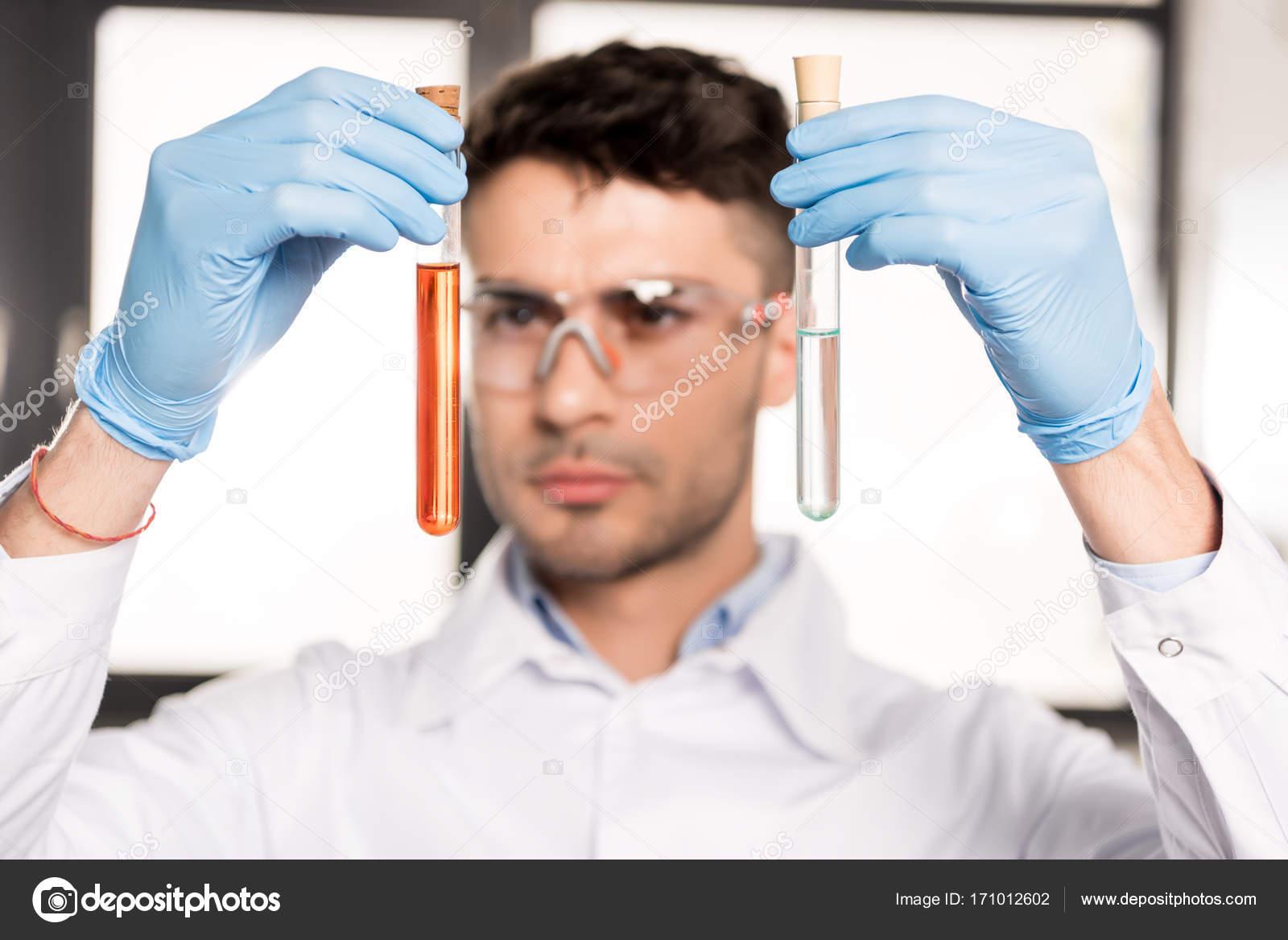 dca7a38f27 Πορτρέτο του νεαρός επιστήμονας σε προστατευτικά γυαλιά κρατώντας σωλήνες  δοκιμής στο ερευνητικό εργαστήριο — Εικόνα από ...