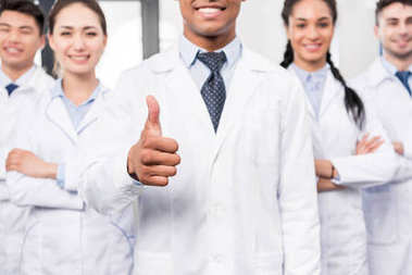 Doctor with team showing thumb up