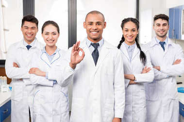 Doctor with team showing ok sign