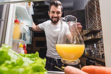 man taking juice out of fridge