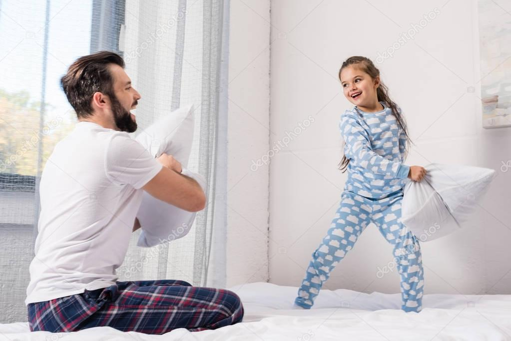 father and daughter fighting with pillows