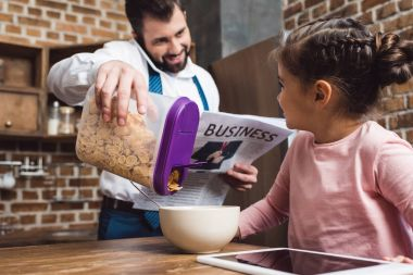 father making cereal breakfast for daughter