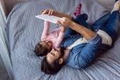 Fotografie otec a dcera pomocí tabletu v posteli