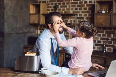 daughter playing with father on kitchen