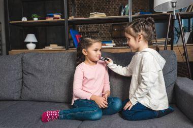 girl doing makeup for sister