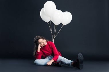 kid sitting tied with bundle of balloons
