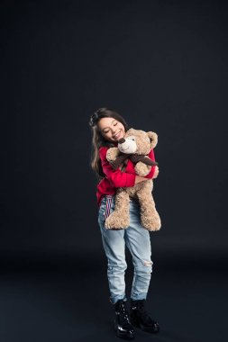 Happy child hugging teddy bear