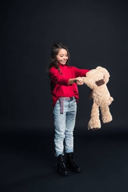 Smiling kid playing with teddy bear