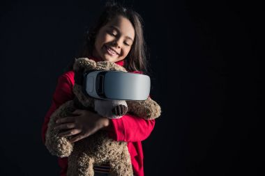 Child putting VR headset on teddy bear