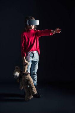 Child in VR headset holding teddy bear