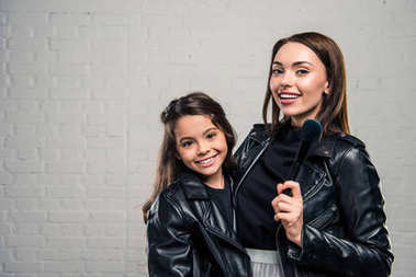 Daughter and mother with makeup brush