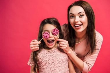 Mother covering daughter eyes with lollipops
