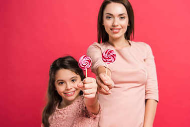 Mother and daughter showing lollipops