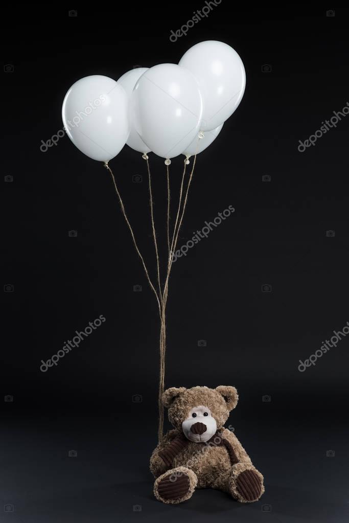teddy bear with helium balloons