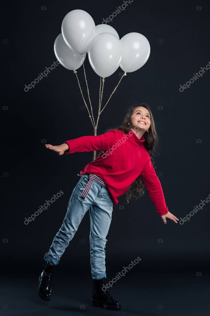 kid imitating flying with balloons