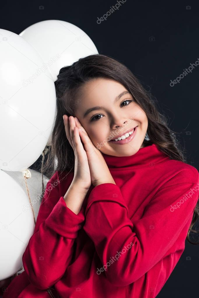 Kid posing with balloons